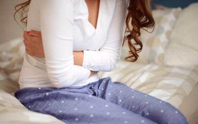young woman sitting in the bedroom on a bed and holding her stomach,abdominal pain