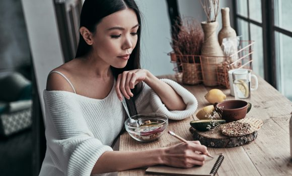 Attractive young woman eating healthy breakfast and writing something down while sitting near the window at home